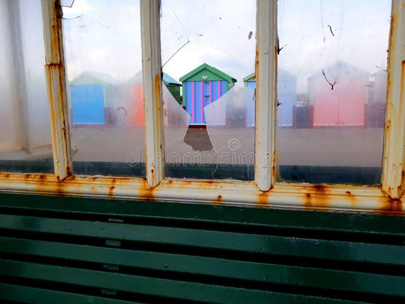Strand förlägga i barack sett igenom slagit fönster arkivfoton
