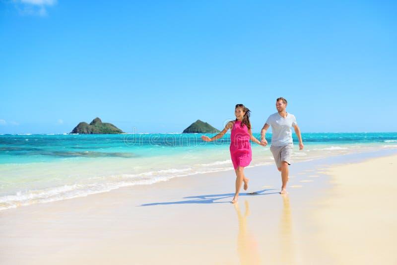 Strand gelukkig paar bij het lopen hebbend pret op Hawaï stock afbeeldingen