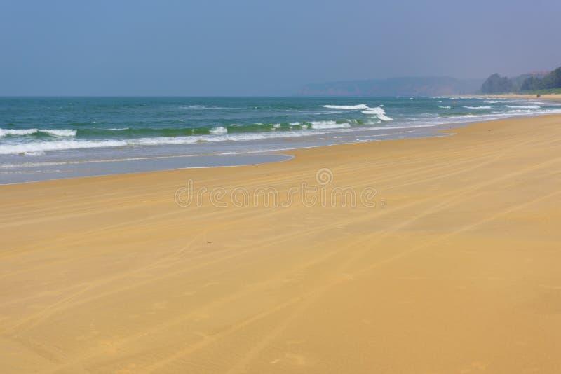 Strand in Goa, Indien Meereswellen und helles mit gelbem Sand stockfoto