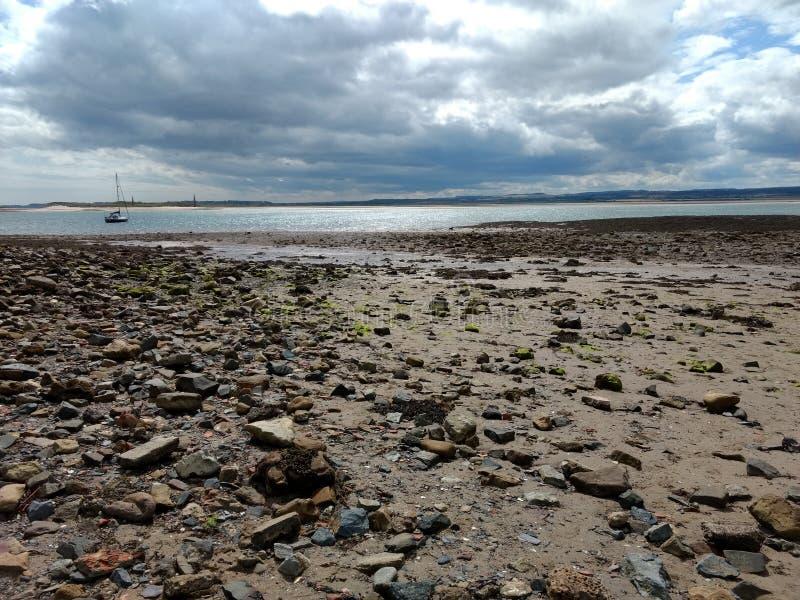 Strand, himmel och yachter på Lindisfarne arkivbilder