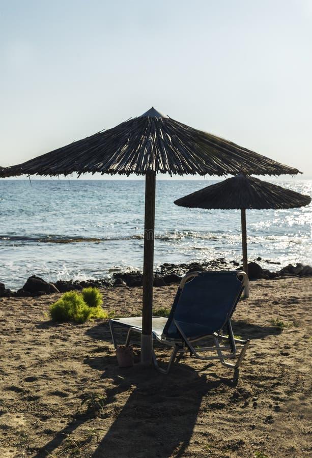 Strand i sunbed sommar med ett paraply och royaltyfri foto