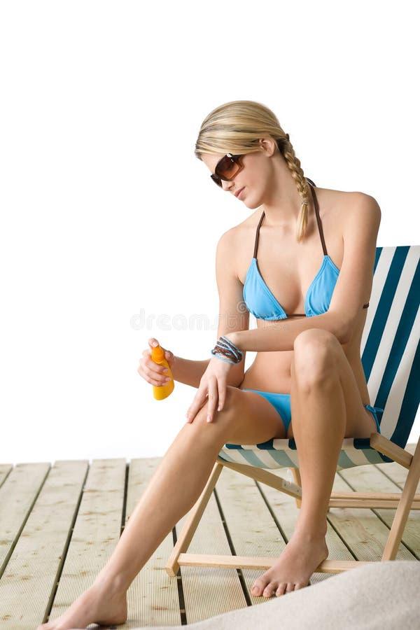Strand - junge Frau wenden Suntanlotion an lizenzfreies stockfoto