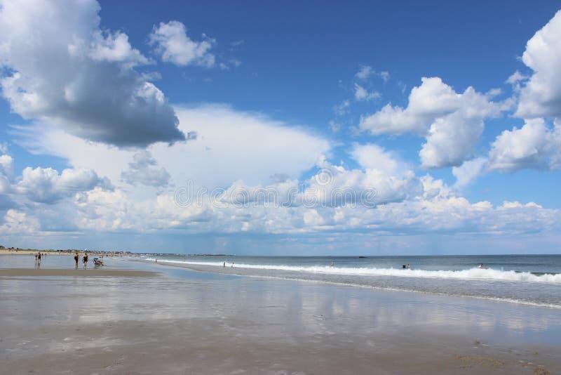 Strand langs oceaan met wolken in de hemel stock afbeeldingen