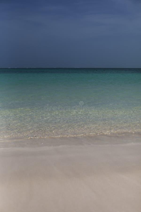 Strand med aquablåtthavet och mörkerhimmel arkivfoton