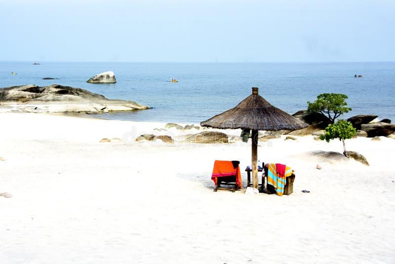 Strand med det afrikanska paraplyet royaltyfria bilder