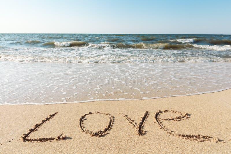 Strand med sandordförälskelse arkivfoto