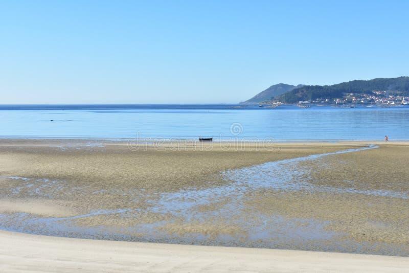 Strand med våt sand, klart blått vatten och ett fartyg Liten kust- by, Galicia, Spanien Solig dag blåttsky royaltyfria foton