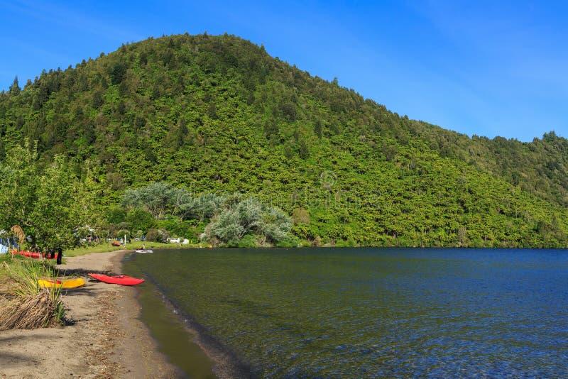 Strand met kajaks, Meer Okareka, Nieuw Zeeland stock afbeeldingen