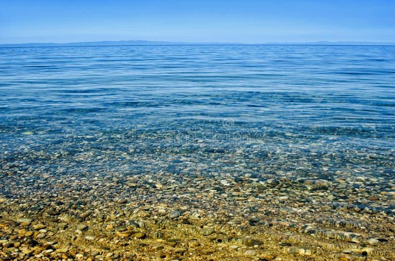 Strand met kiezelsteen en turkoois water onder blauwe hemel royalty-vrije stock afbeelding