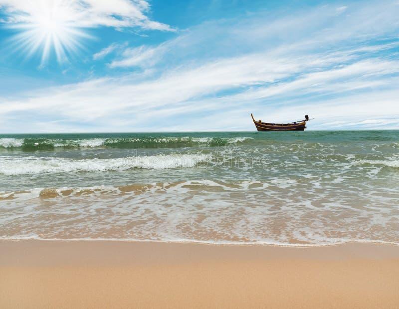 Strand met over zonlicht en vissersboot royalty-vrije stock foto