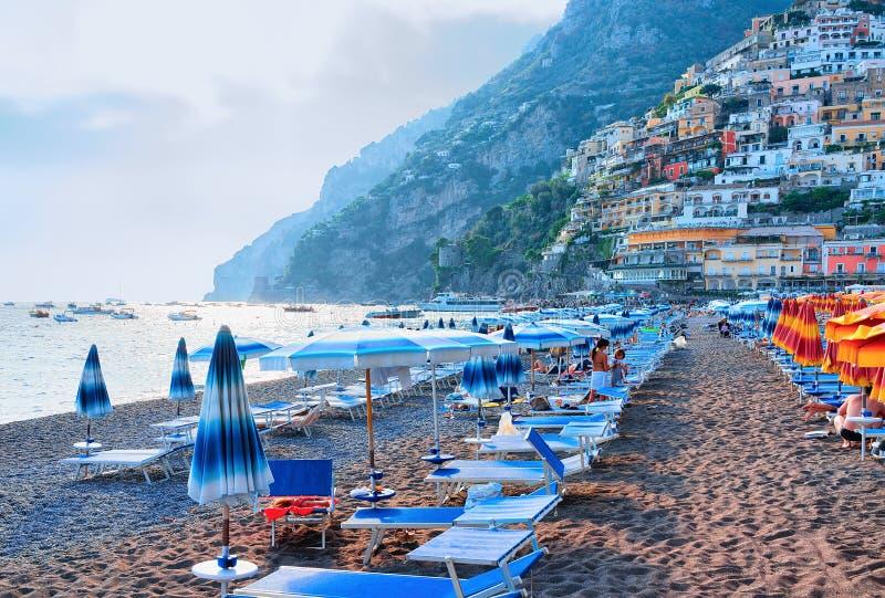 Strand met paraplu's in de stad en Thyrreense Zee van Positano stock afbeeldingen