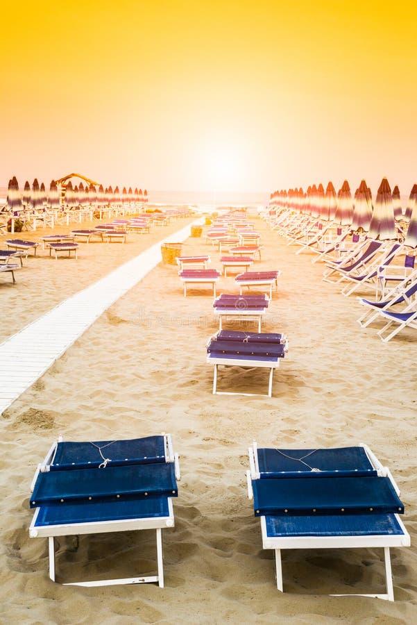 Strand met paraplu's en sunbeds stock afbeelding