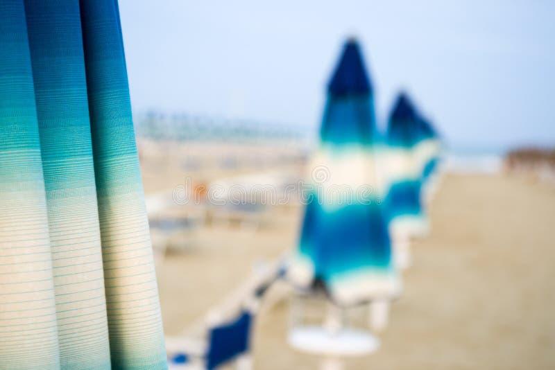 Strand met paraplu's en sunbeds stock afbeeldingen