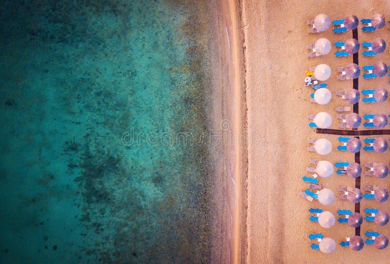 Strand met paraplu's en sunbeds luchtmening stock fotografie