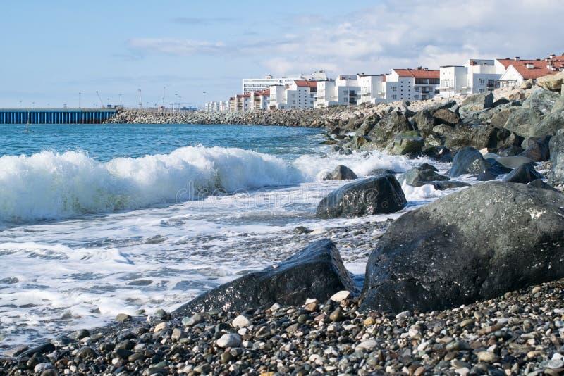 Strand met reusachtige rotsen en golven op de achtergrond van huizen en watergebied op een Zonnige dag royalty-vrije stock afbeelding