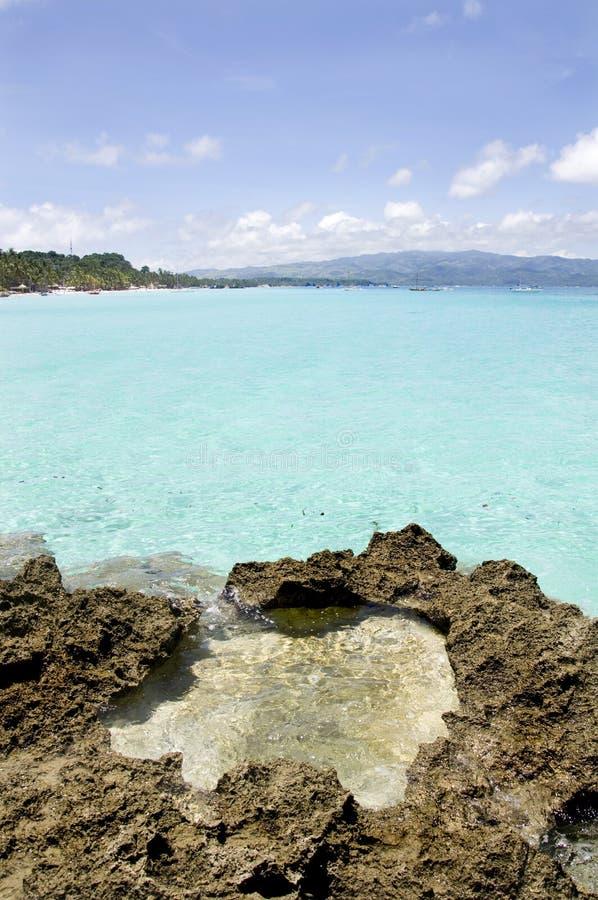 Strand met rotsen in water stock afbeelding