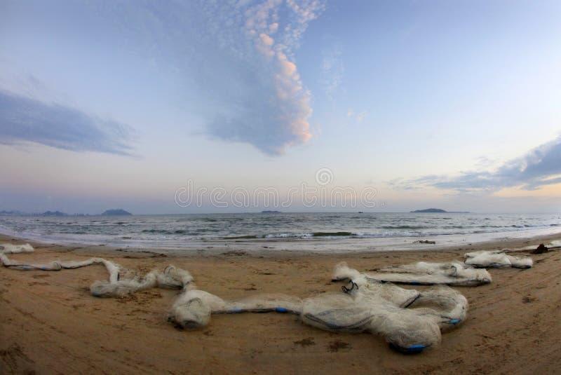 Strand met visserijnetwerken stock fotografie