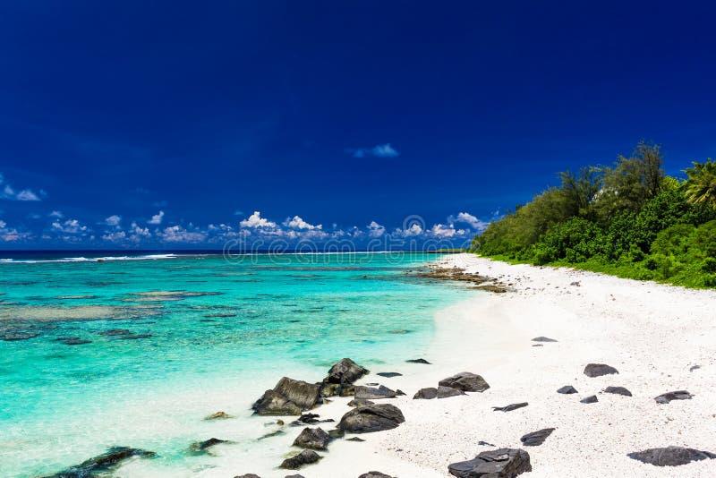 Strand met wit zand en zwarte rotsen op Rarotonga, Cook Islands royalty-vrije stock fotografie