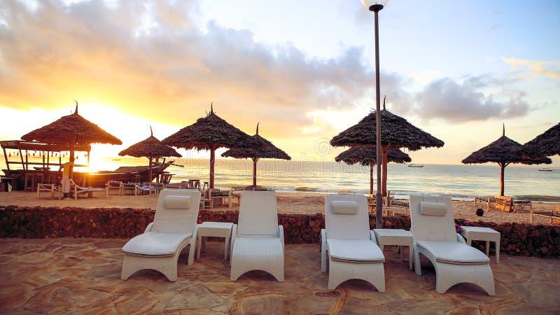 Strand met zonlanterfanters en een plaats voor rust bij zonsondergang Een beauti stock fotografie