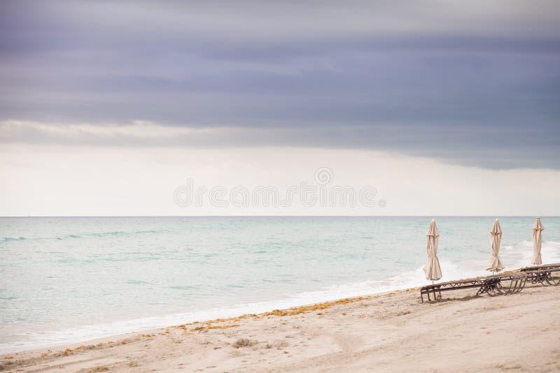 Strand in Miami, FL Gevouwen paraplu's op het zandstrand bij de oceaan Leeg strand Overzeese kust Mening van hierboven De achterg royalty-vrije stock foto
