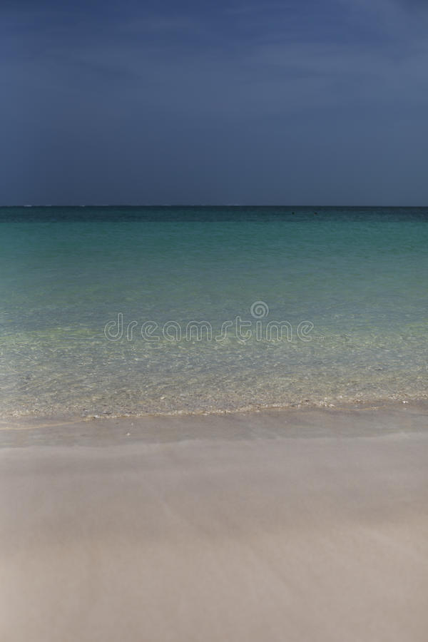 Strand mit blauem Ozean und bewölktem Himmel des Aqua stockfotos