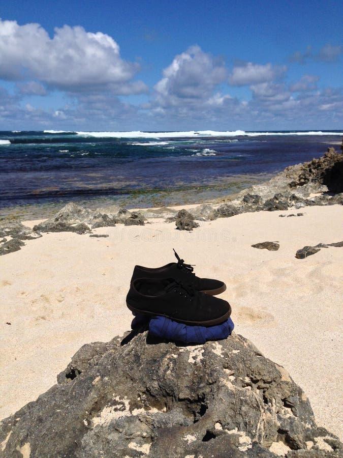 Strand mit dem Hemd und Schuhen angehäuft auf Felsen lizenzfreie stockfotos