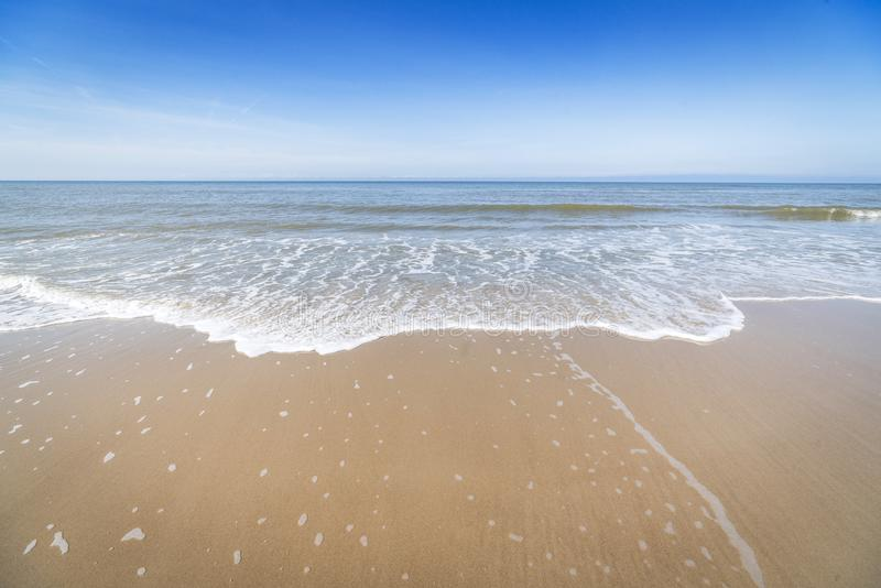 Strand mit den kleinen Wellen, die auf das Ufer hereinkommen stockfotos