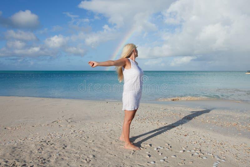 Strand mit Regenbogen und Mädchen stockfotos