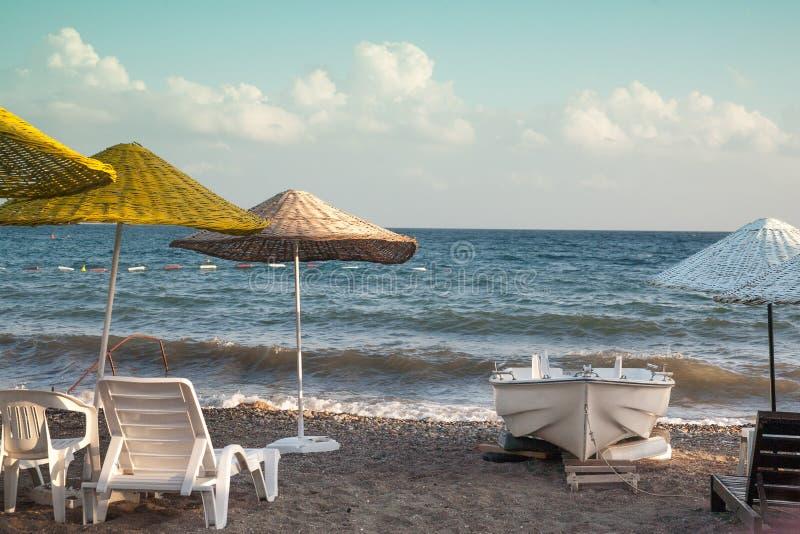 Strand mit Regenschirmen und Sonnenruhesesseln Kleines Boot auf dem Ufer lizenzfreie stockfotografie