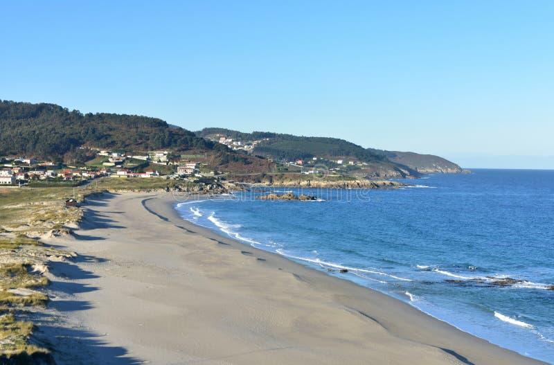 Strand mit Sanddünen und Felsen Blaues Meer mit kleinen Wellen, sonniger Tag, klarer Himmel Morgenlicht, Galizien, Coruna, Spanie lizenzfreie stockbilder