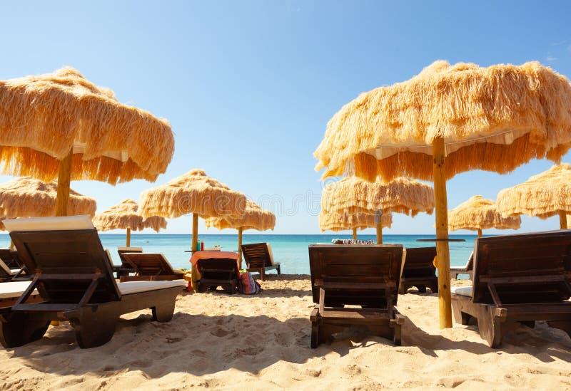 Strand mooie met stro bedekte paraplu's en turkooise overzees stock afbeeldingen