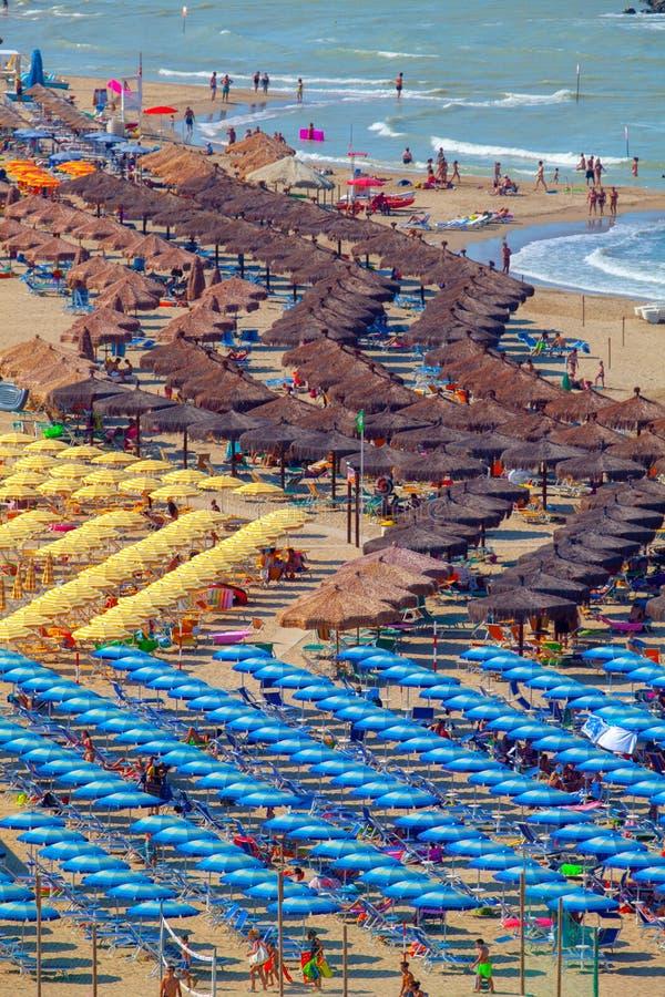 Strand- och Adriatiska havet kust med en m?ngd som ?r seamsless av strandparaplyer, deckchairs och semesterfirare arkivfoto