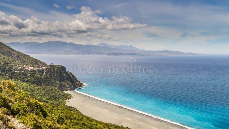Strand och by av Nonza på Cap Corse i Korsika royaltyfri bild