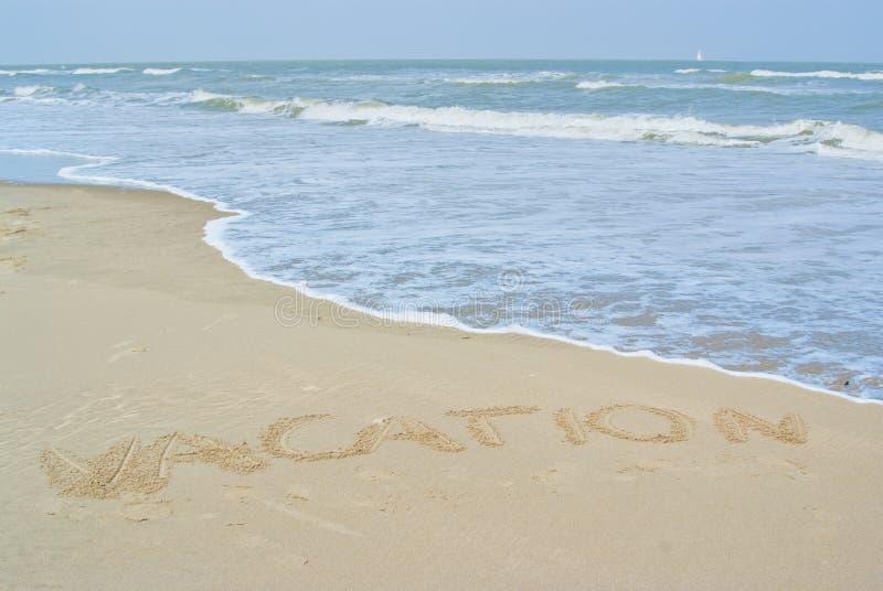 Strand och den skriftliga ordsemestern i sanden royaltyfri foto