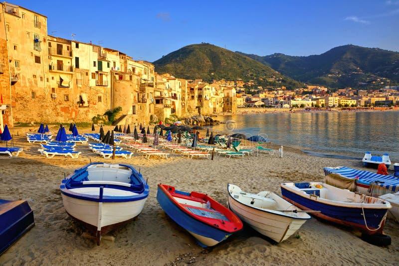 Strand och gammal hamn på solnedgången med fiskebåtar, Cefalu, Sicilien, Italien royaltyfria foton
