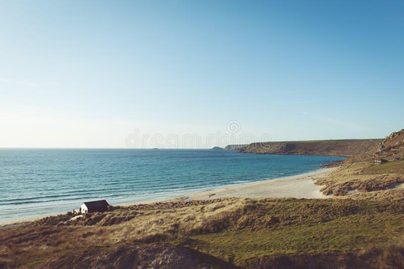 Strand- och klippasida med en kabin nära kusten royaltyfri foto