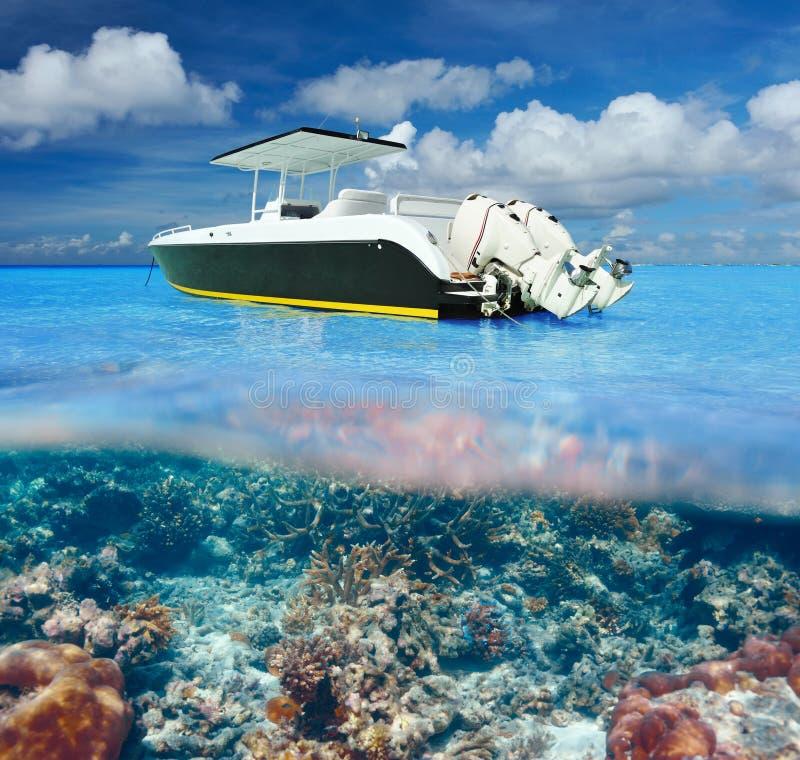 Strand och motoriskt fartyg med undervattens- sikt för korallrev royaltyfri bild