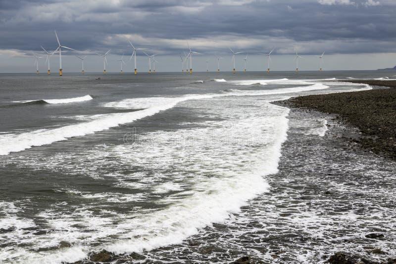 Strand- och vindturbiner på munnen av flodutslagsplatser arkivfoton