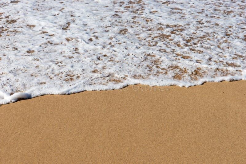 Strand overzees zand met een zachte golf van branding royalty-vrije stock afbeeldingen