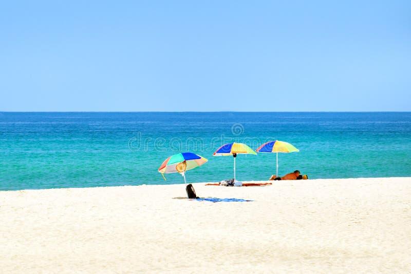 Strand overzeese de zomerparaplu's De achtergrond van het reisstrand royalty-vrije stock afbeelding