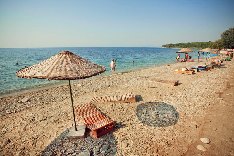 Strand på turkiska semesterortsolparaplyer och folk som simmar i vatten för lugna hav royaltyfria bilder