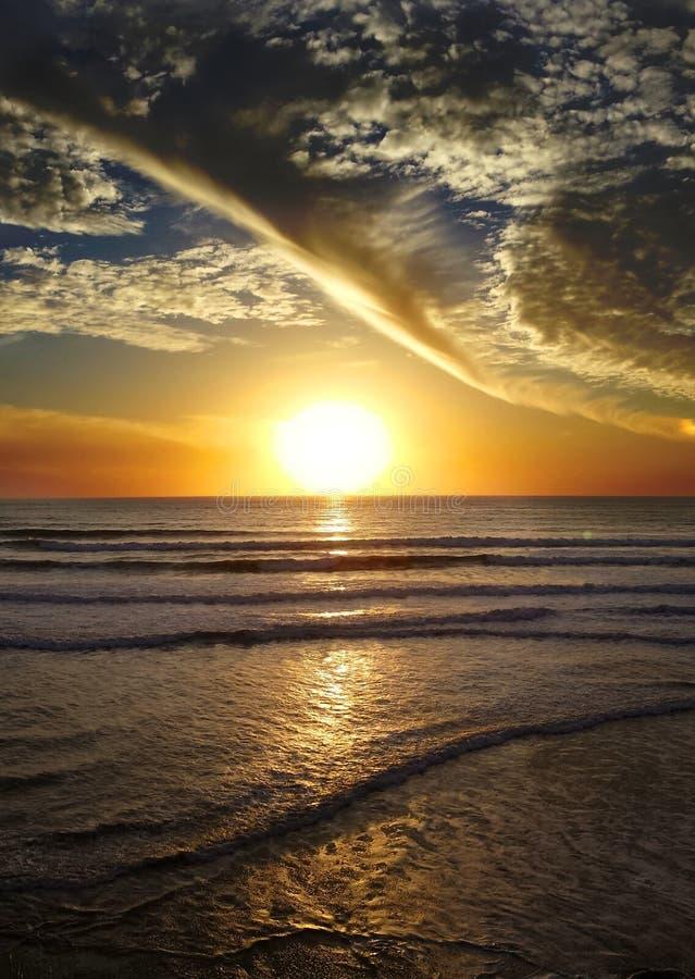 Strand, sol och moln arkivbild