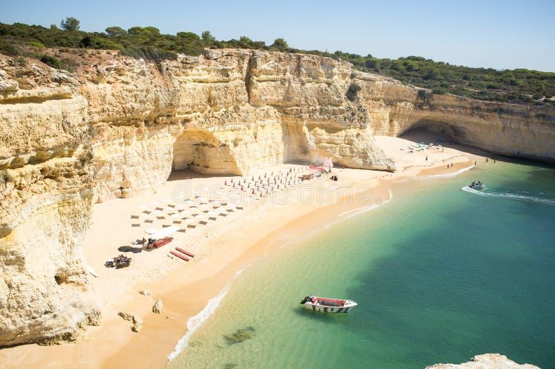 Strand som är klar att koppla av turister på Praia da Marinha arkivfoton