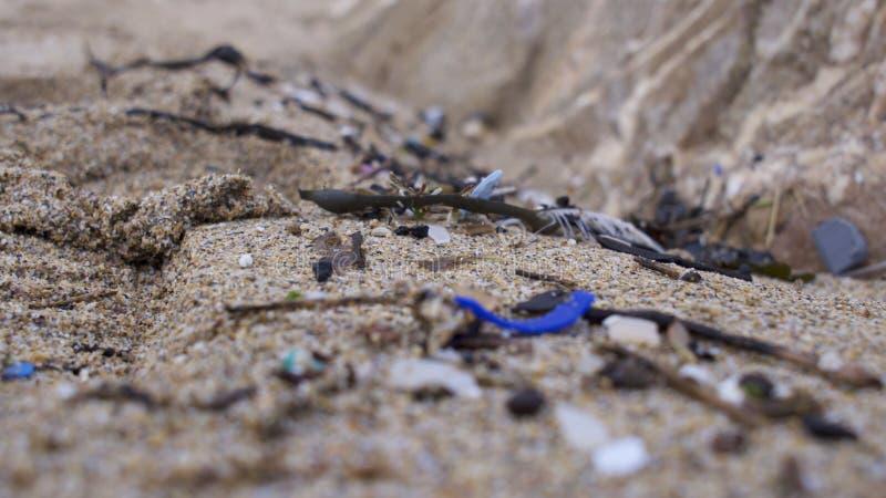 Strand som förorenas med plast- royaltyfri foto