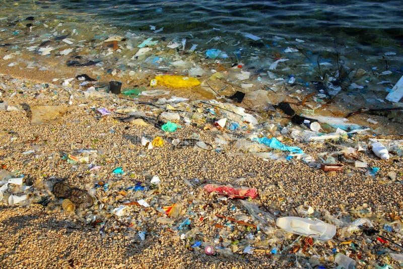 Strand som förorenas med plast- arkivfoto