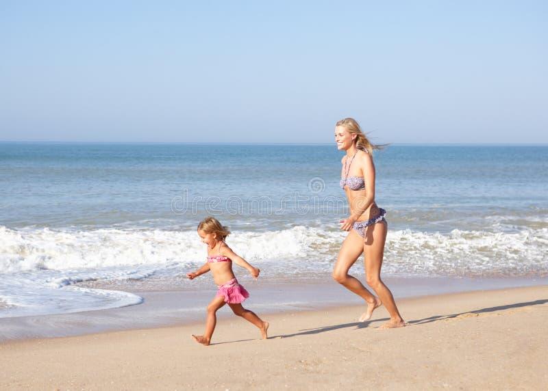 strand som jagar flickamoderbarn arkivbild
