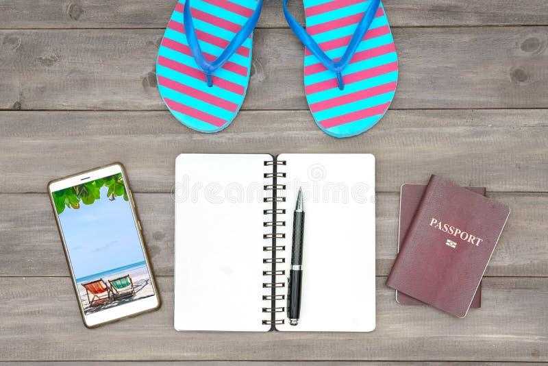 Strand som reser planera begrepp Bästa sikt av sandaler, passet, smartphonen och den tomma anteckningsboken på träbakgrund Lägenh arkivbilder