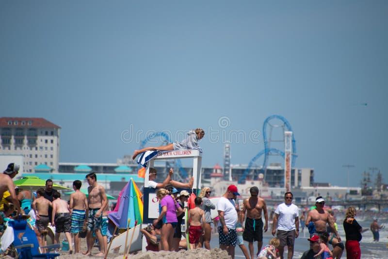 Strand som trängas ihop med folk på en solig molnfri dag En kvinnlig livräddare är sett lägga på taket av en livräddareställning  arkivbild