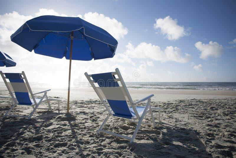 Strand-Stühle und Regenschirm in dem Ozean stockbilder