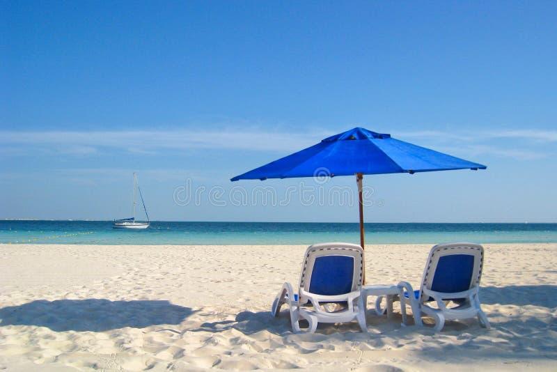 Strand-Stühle und Regenschirm durch das Meer stockfoto